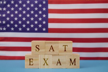 SAT Exam in WOoden blook letters on US flag.