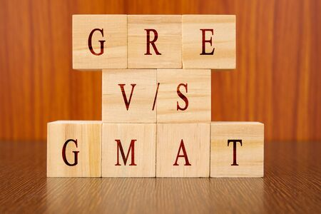 Concept of GRE vs GMAT Exam differences in wooden block letters on table