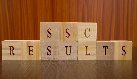 Concept of SSC exam Results conducted in India, in wooden block letters on table.