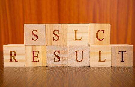 Concept of SSLC exam Results conducted in India, in wooden block letters on table.