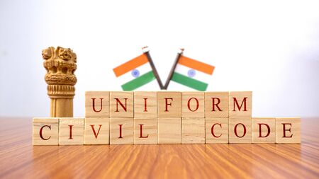 Concept of One law for all called Uniform Civil code or UCC in Indian constitution in wooden block letters and Indian flag as a background