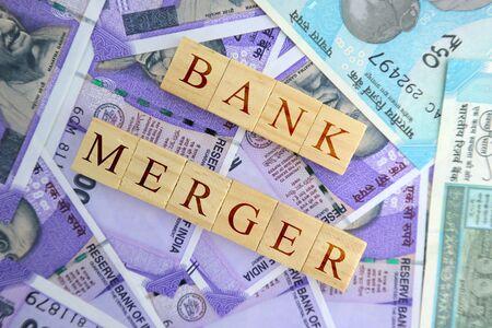 Konzept der Bankfusion in Holzblöcken auf indischen Banknoten.