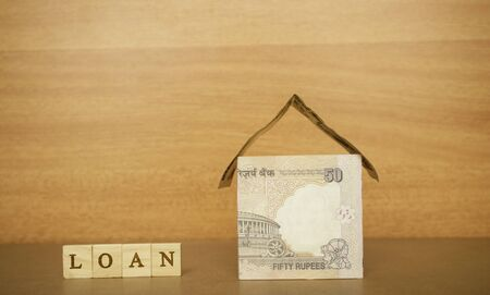 House made from the Indian currency notes and Home Loan in wooden block letters on wooden background.