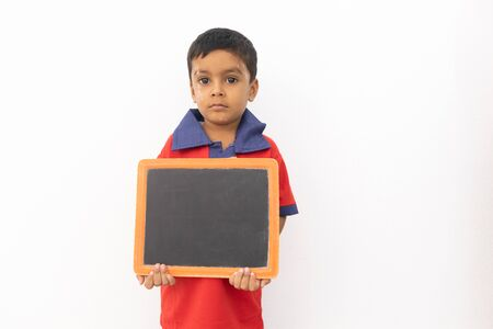 Concept of child protest showing with young boy holding black slate on isolated background