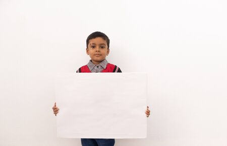 Concept of child protest showing with young boy holding large white placard on isolated background Stock fotó