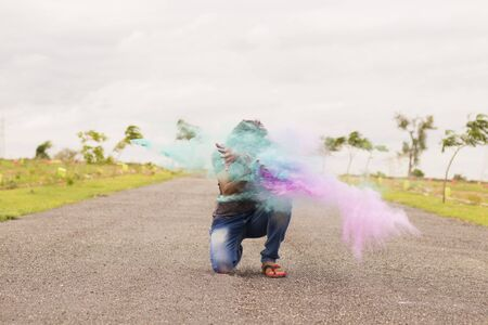 Concept of holi festival, Man exploding colorful powders in hands on road