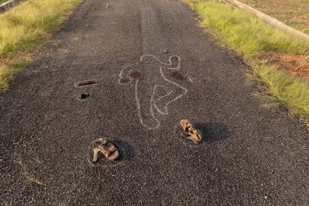 High angle view of Crime scene chalk outline of victim dead body on Road with blood and evidences, Concept of murder investigation.