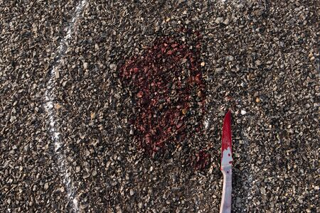 Close up of Crime scene chalk outline of victim dead body on Road with bloody knife and blood. 版權商用圖片