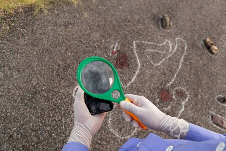 Detective or investigator verifying the fingerprints on mobile using magnifier and Chalk outline dead body as a background