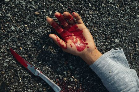 Close up of hand with blood and bloody knife on road