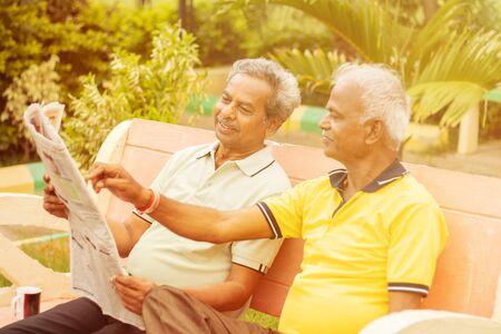 Two happy senior men reading newspaper at park outdoor - elderly friends enjoying moring news - Concept of happy older men lifestyle.