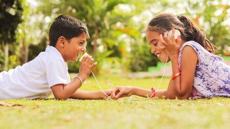 Zwei Kinder haben Spaß beim Spielen mit Schnurtelefon im Park während des Urlaubs - Konzept der Gehirnentwicklung und Geselligkeit durch Spielen im Freien in der technologiegetriebenen Welt.