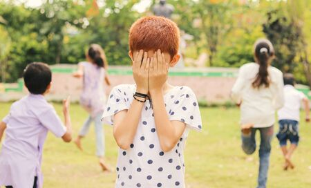 Childrens playing hide and seek at park - Multi ethnic kids playing outdoor games