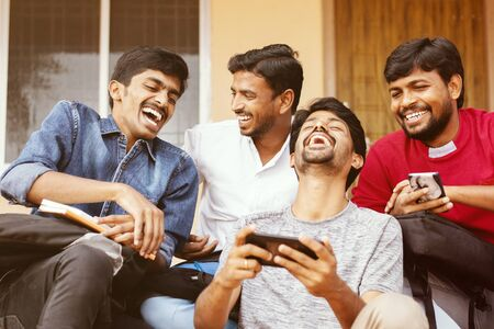 Group of happy young college students by looking at mobile phone laughing loudly at university campus - Millennials enjoying online video content or social media by watching smart phone.