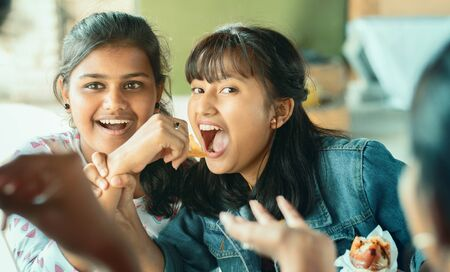 Teenager trying to take or grab food from friend - young girl playfully fighting for snacks with her friend - concept of friends having fun while having food at college restaurant. Banque d'images