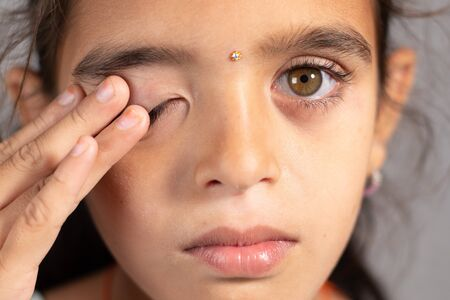 Extreme close up of child rubbing her eyes - concept showing to prevent and Avoid touching your eyes. Protect from COVID-19 or coronavirus infection or outbreak - Don t Touch Your eyes.