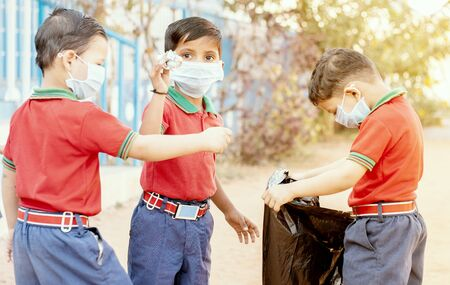 Group of children volunteers picking up, cleaning trash at school - concept of school kids or classmates collecting trash, charity environment.