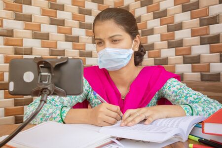 Concept of homeschooling and e-learning, College girl with medical mask listing virtual class on mobile during covid-19 or coronavirus pandemic lock down. 版權商用圖片