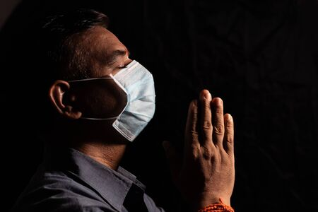 Man with medical mask praying to god by closing eyes in dark room to protect or save from covid-19 or coronavirus crisis - spirituality and Surrender concept.
