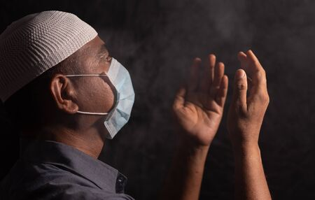 Muslim Man with medical mask and cap praying to god in dark room to protect or save from covid-19 or coronavirus crisis - spirituality and Surrender concept.