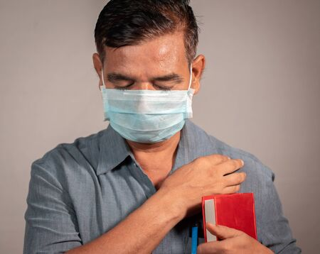 50s man holding bible and praying god with medical face mask wearing to protect from covid-19 or coronavirus pandemic - Concept of hope, peace during tough quarantine times.