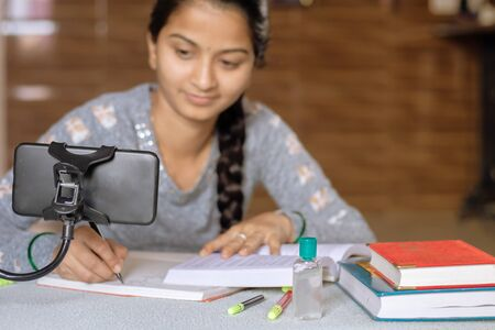 Selective focus of Mobile, Concept of e-learning at home due to covid-19 or coronavirus isolation - Young college girl taking notes by looking into virtual class on mobile due to isolation.