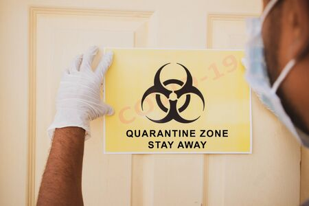 Frontline worker applying banner of Covid-19 or coronavirus quarantine zone stay away infront of the door at hospital as caution note