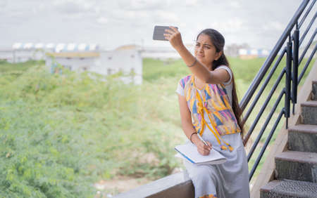 College girl outside home watching online class due to slow internet connection - concept of network issue at remote places and problem of virtual class or distance learning during pandemic.