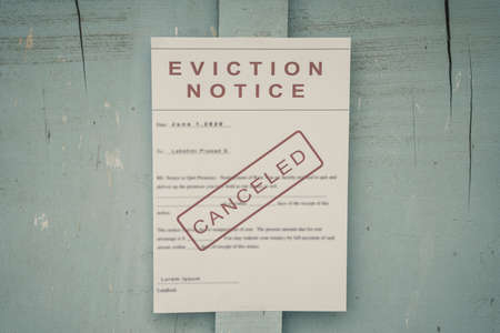 Canceled Foreclosed or eviciton notice on a main door with blurred details of a house with vintage filter