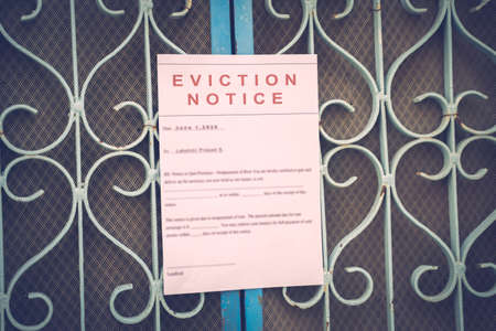 Foreclosed or eviciton notice on a main door with blurred details of a house with vintage filter Standard-Bild