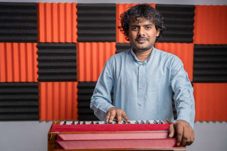 Young musician playing Indian music instrument Harmonium in studio.