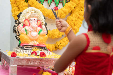 kid praying by closing eyes infront of god Ganesha idol by holding or offering incense in hand during ganapati festival celebration at home.
