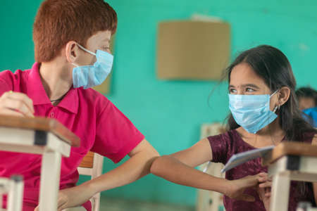 Two kid in medical mask at classroom greeting each other with elbow bumps while maintaining socail distance at school - Concept of school reopen, back to school safety measures and new normal lifestye Banque d'images