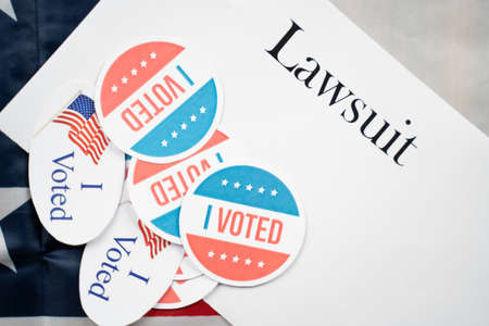 I voted stickers on Lawsuit paper with US flag as background - Concept of lawsuits in USA election