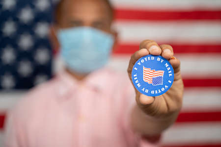 Man in medical mask showing I voted by mail sticker with US flag as background - Concept of mail in voting at USA election
