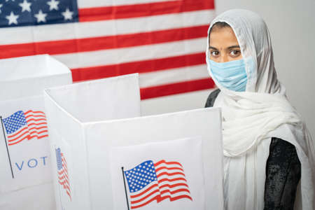 Girl with Hijab or head covering and mask worn at polling booth looking at camera with US flag as background - Concept of US election
