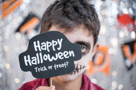 Kid hloding Halloween booth prop infront of spooky face - concept of halloween trick or treat.