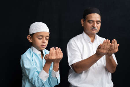 Muslim father and son in medical mask praying or performing Salah o protect from coronavirus or covid-19 by sitting.