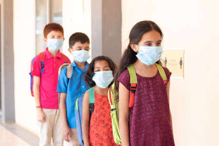 School childrens standing line in front of class while maintaining social distance outside classroom with medical mask wearing - concept of covid-19 or coronavirus safety measures at school
