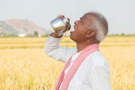 Thirsty Indian farmer drinking water from steel tumbler or Chambu on hot sunny day at agriculture field.
