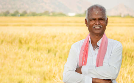 Portrait of Confident smiling Indian farmer with arms crossed standing in front of agriculture farmland looking camera with copy space