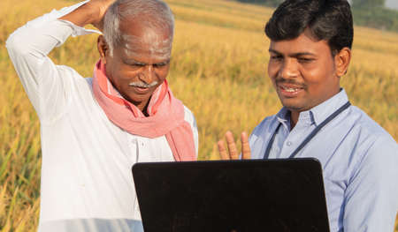 Confused Indian farmer Scratching his head while banker or corporate government officer discussing on laptop about crop yield, credit and loan subsidy at agriculture farmland during hot sunny day.