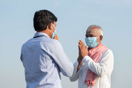Low angle view, Farmer greeting to banker or corporate government officer by doing namaste while both worn face mask due to coronavirus covid-19 pandemic meeting near agriculture farmland
