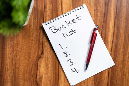 Pen and book with written Bucket list on note book for 2021 new year