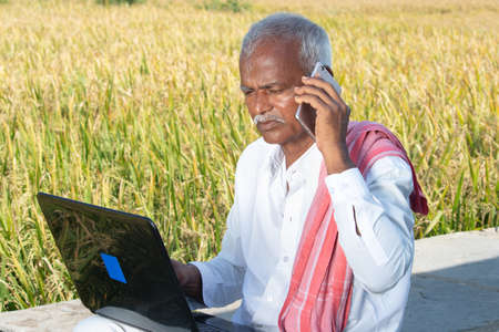 Indian farmer talking on mobile phone while busy looking into laptop near the agriculture farmland - concept of farmer using technology, internet in rural India Banque d'images