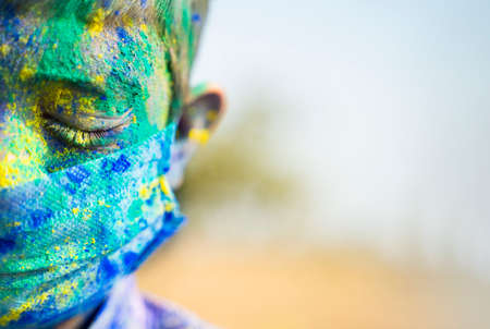 Close up half face head shot of Young boy with medical face mask played holi the festival of colours and looking into camera - concept of holi celebration during virus pandemic 免版税图像