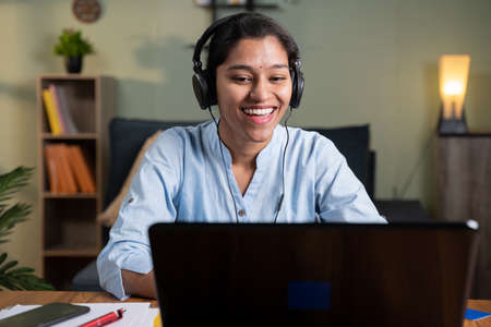 Happy smiling young Business woman with headphone in video call on laptop busy talking - concept of online chat, distance webinar, video conference during work from home 免版税图像