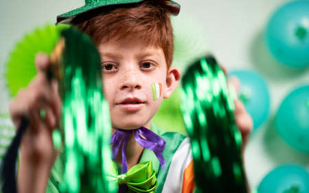 Cheerful happy dancing Young kid with green dress on decorated background - concept of saint Patricks day celebration. 免版税图像