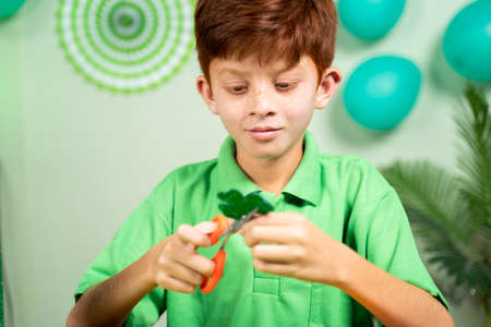 Young kid busy in preparing shamrock leaves for saint patricks day festival celebrations at home.