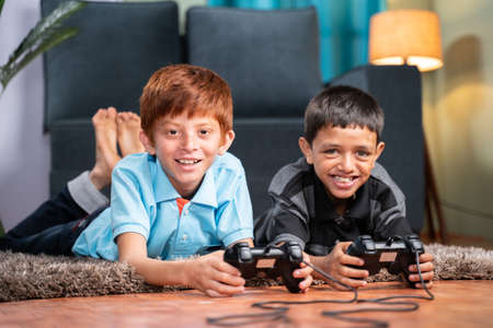 Two multi ethnic kids busy in playing videogame using gamepad while lying on floor at home - Concept of children unhealthy playing position and new technology addiction. 免版税图像
